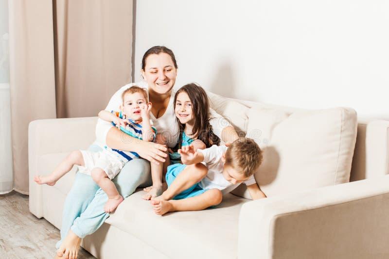 Donna con i suoi bambini sul sofà fotografia stock libera da diritti