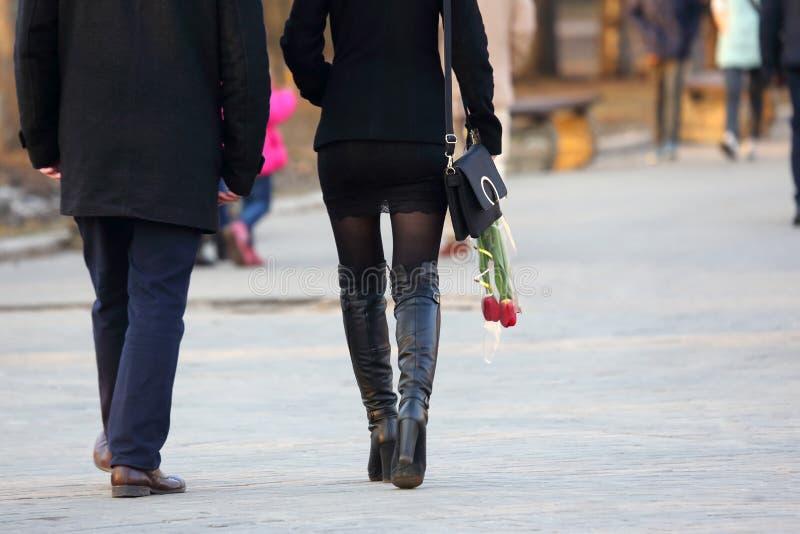 Donna con i tulipani dei fiori in sua mano, camminante accanto all'uomo immagini stock libere da diritti