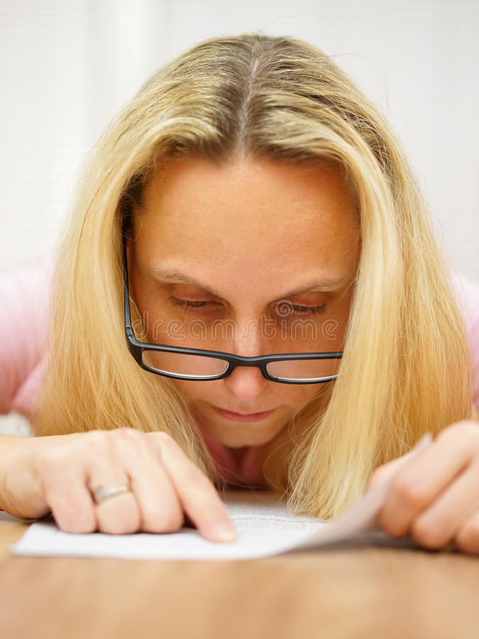 Donna con i vetri che legge documento molto messo a fuoco ed indicare immagini stock libere da diritti
