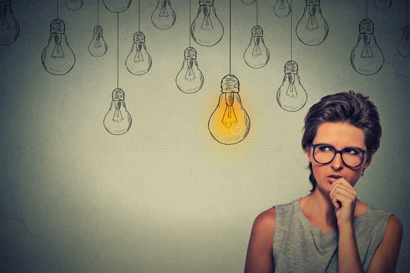 Donna con i vetri che pensa duro cercando giusta soluzione immagini stock