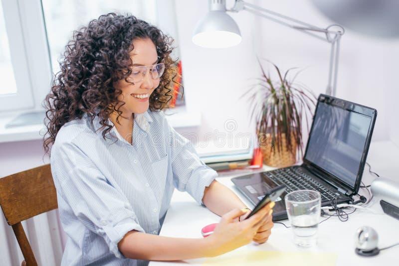 Donna con i vetri d'uso dei capelli ondulati che esaminano i photoes divertenti sul cellulare immagini stock libere da diritti