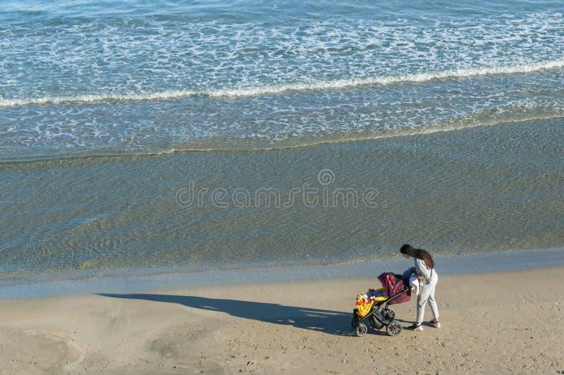 Donna con il bambino addormentato sul mare fotografia stock
