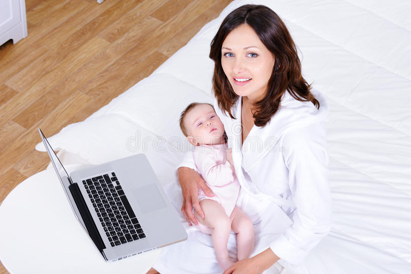 Donna con il bambino che si siede su una base con il computer portatile immagini stock libere da diritti