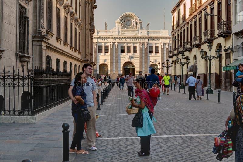 Donna con il bambino che vende prodotto ai turisti in Lima Peru centrale fotografie stock libere da diritti