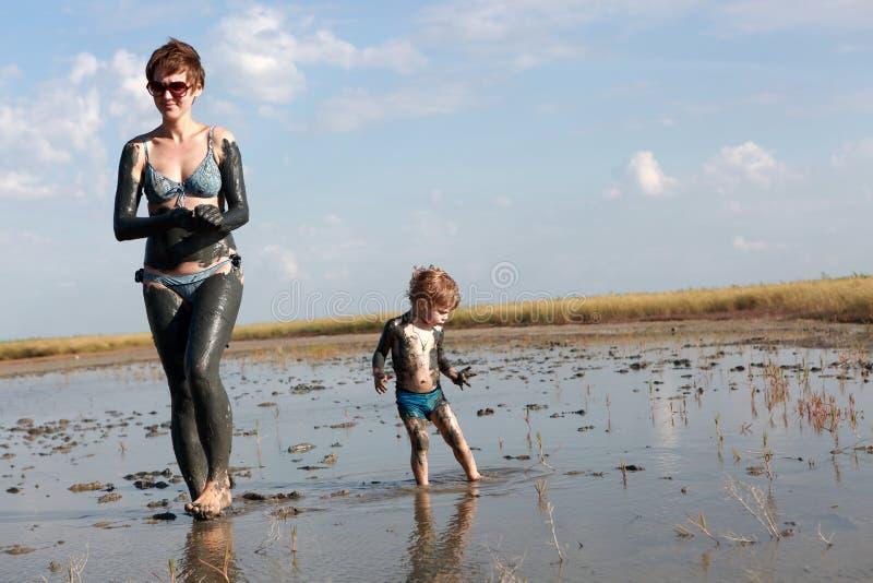 Donna con il bambino in fango curativo immagine stock