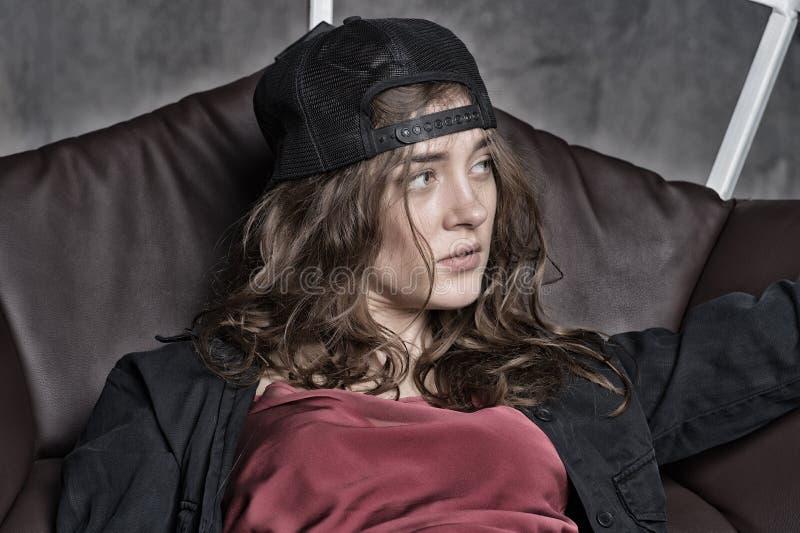 Donna con il berretto da baseball d'uso dei capelli lunghi di nuovo alla parte anteriore fotografia stock libera da diritti
