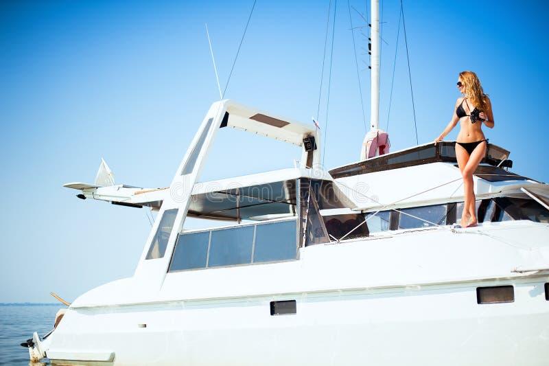 Donna con il binocolo che sta su un grande yacht bianco nel mare immagine stock libera da diritti