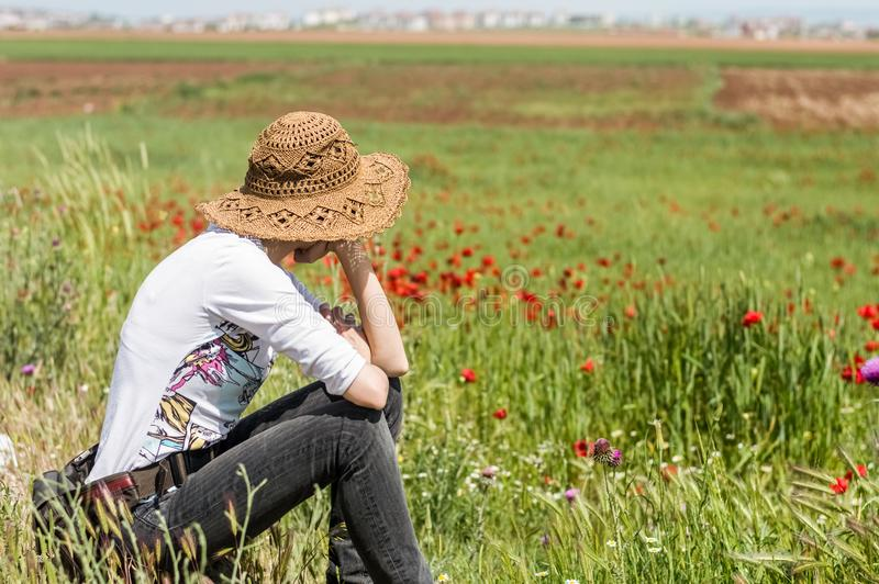 Donna con il cappello che si siede in un prato in pieno dei fiori, godendo della natura fotografia stock