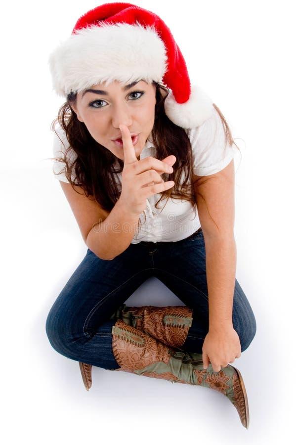 Donna con il cappello di natale e chiedere di mantenere silenzioso fotografie stock libere da diritti