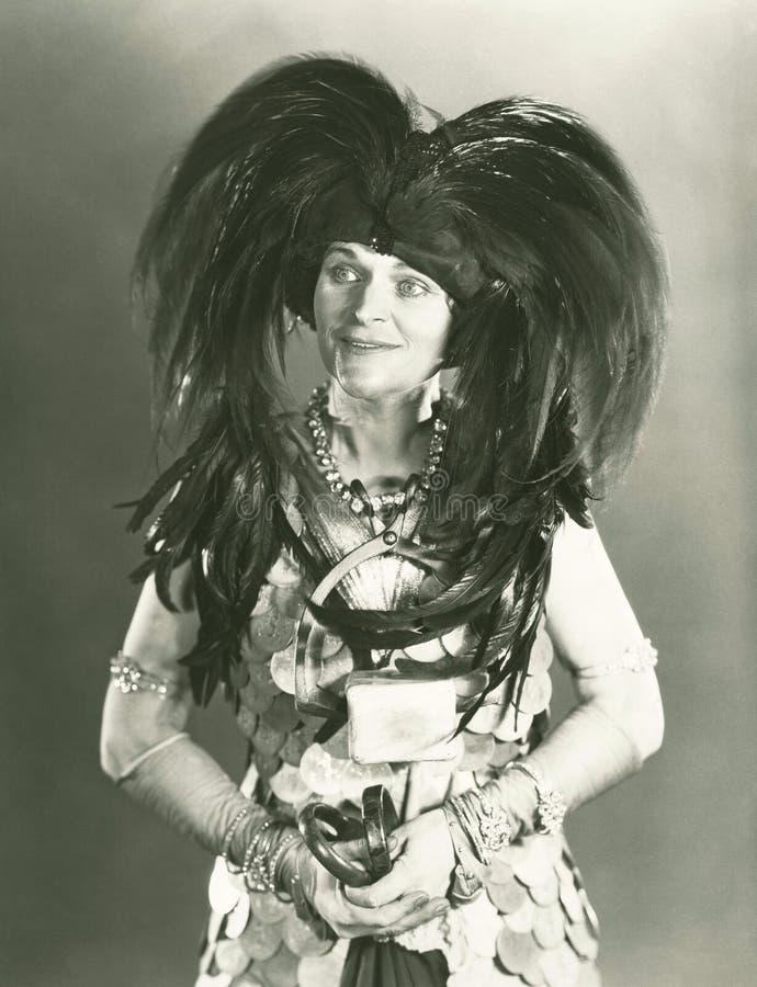 Donna con il cappello messo le piume a fotografia stock