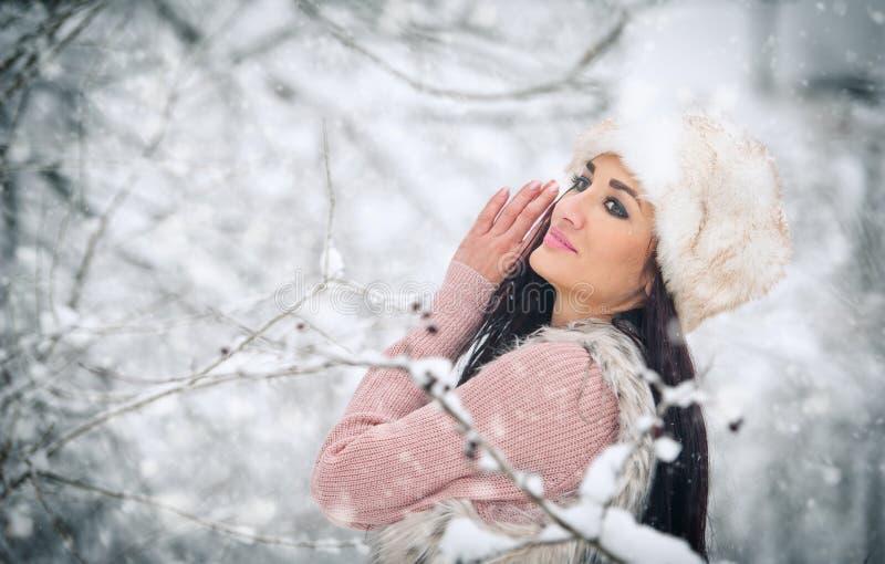 Donna con il cappuccio bianco della pelliccia che sorride godendo del paesaggio di inverno nella vista laterale della foresta del fotografia stock