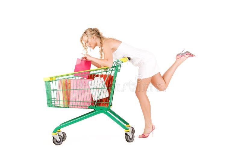 Donna con il carrello sopra bianco fotografia stock