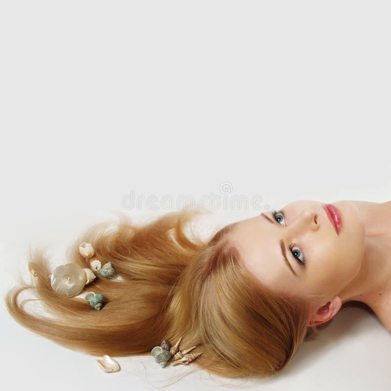 Donna con il cockleshell marino in capelli fotografia stock