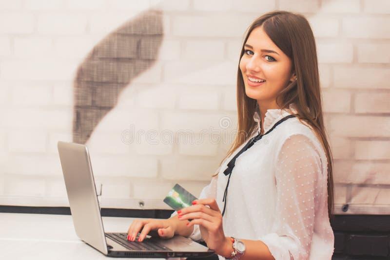 Donna con il computer portatile e carta di credito che fa acquisto online fotografia stock libera da diritti