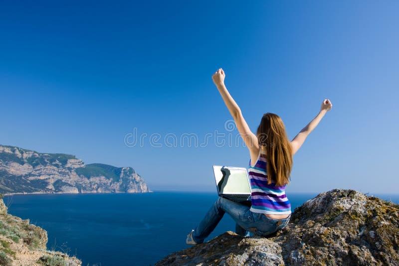 Donna con il computer portatile ed il mare fotografia stock
