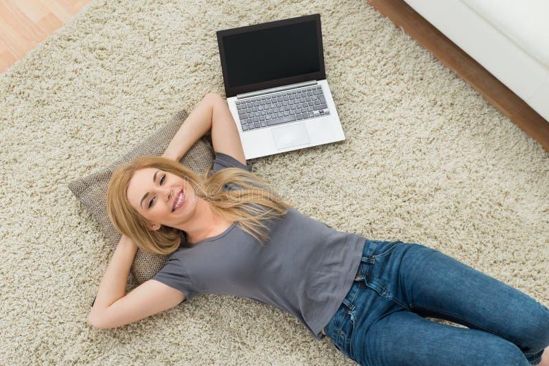 Donna con il computer portatile in salone fotografia stock