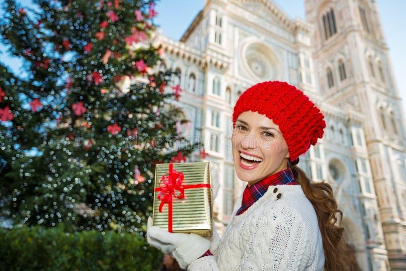 Donna con il contenitore di regalo che sta l'albero di Natale vicino a Firenze fotografia stock libera da diritti