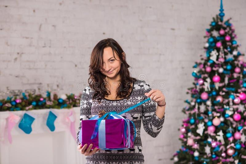 Donna con il contenitore di regalo vicino alle decorazioni di natale immagini stock libere da diritti