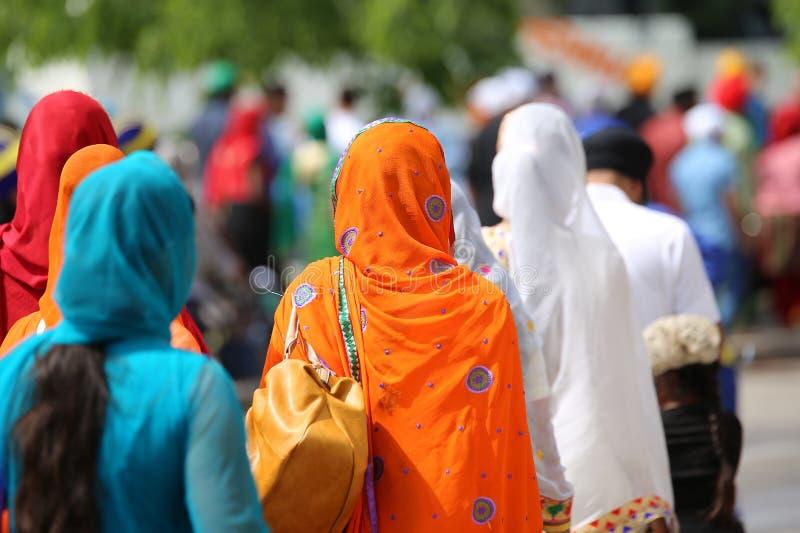 donna con il copricapo arancio del foulard durante la riunione del peop fotografie stock