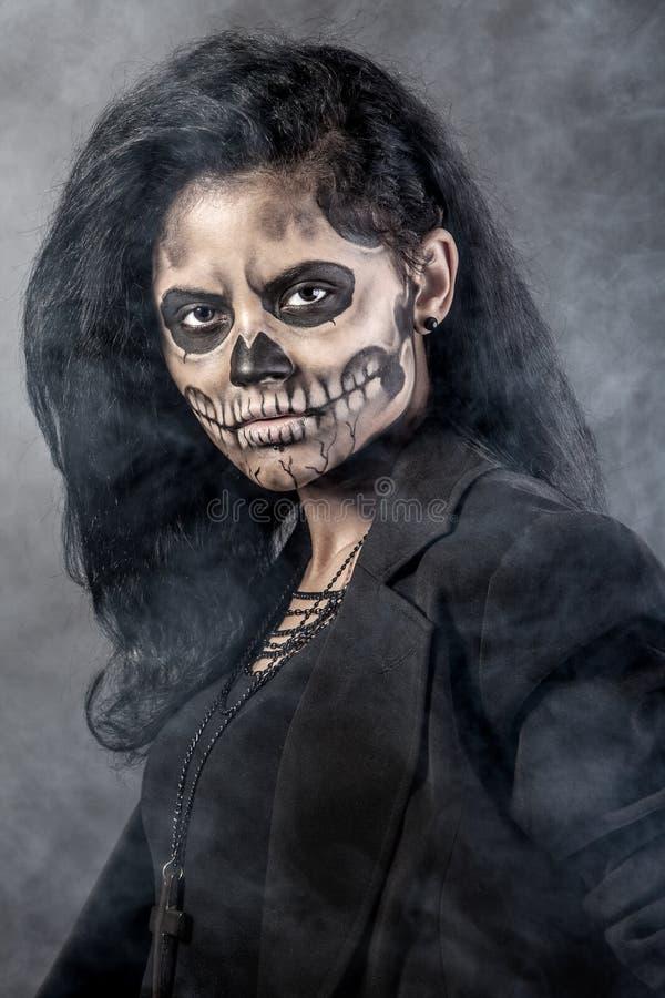 Donna con il cranio della mascherina. Arte del fronte di Halloween fotografia stock