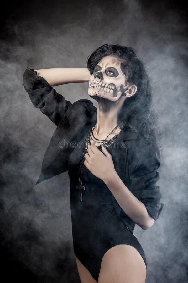 Donna con il cranio della mascherina. Arte del fronte di Halloween immagini stock