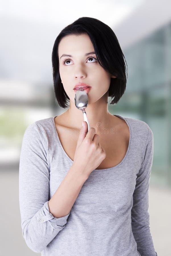 Donna con il cucchiaio nella sua bocca fotografia stock libera da diritti