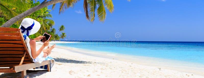 Donna con il cuscinetto di tocco sulla spiaggia tropicale fotografia stock libera da diritti