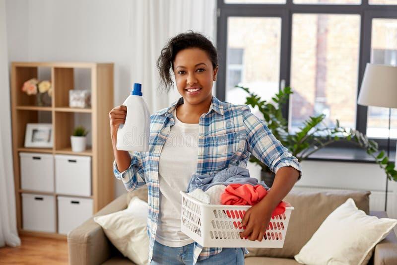 Donna con il detersivo di lavanderia e del canestro a casa fotografia stock libera da diritti