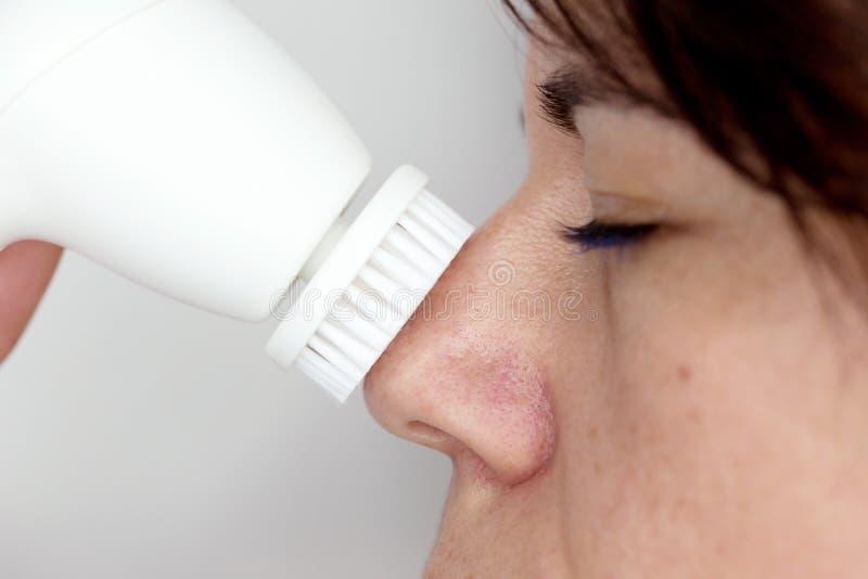 Donna con il dispositivo di pulizia della pelle immagine stock