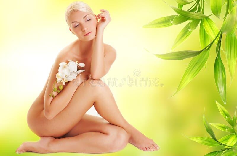 Donna con il fiore bianco dell'orchidea immagini stock