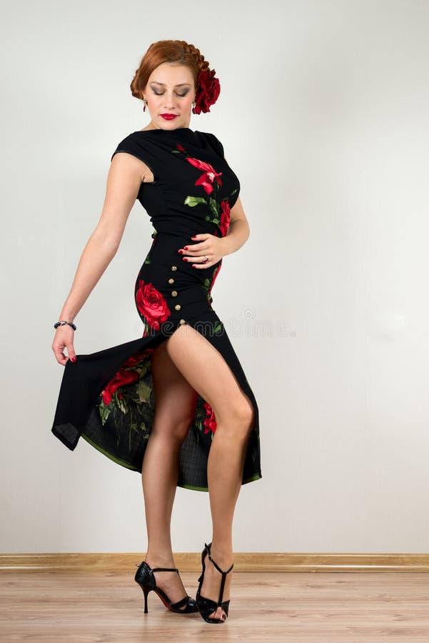 Donna con il fiore rosso in vestito nero con ballare delle scarpe immagini stock