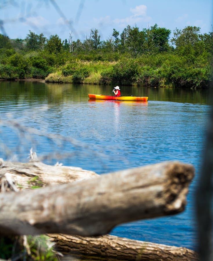 Donna con il kayak della maglia di sicurezza da solo su un fiume calmo fotografia stock