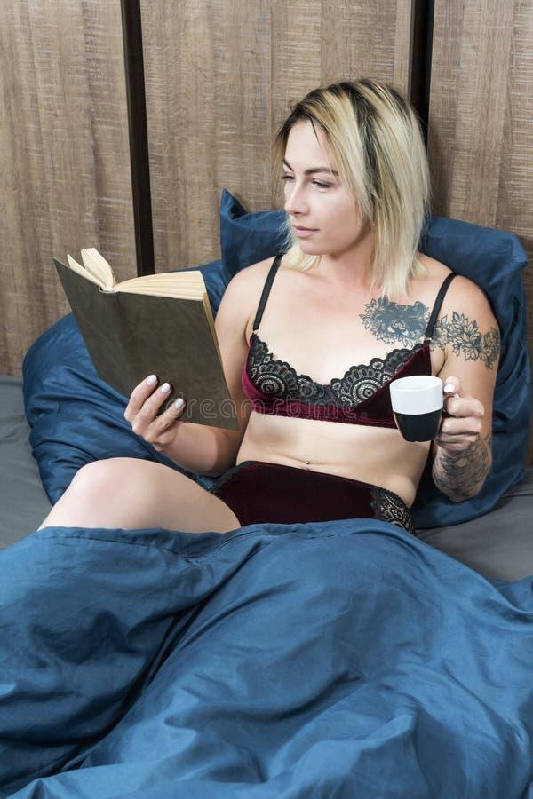 Donna con il libro di lettura della tazza di caffè fotografia stock