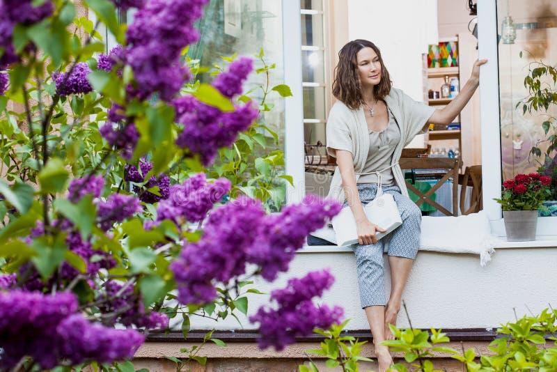 Donna con il libro sul davanzale della finestra in giardino immagini stock libere da diritti