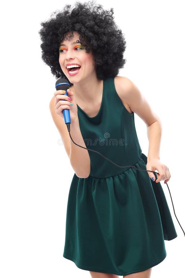 Donna con il microfono della tenuta dell acconciatura di afro