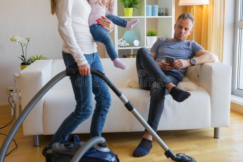 Donna con il piccolo bambino che fa governo della casa mentre uomo che si siede in strato immagine stock libera da diritti