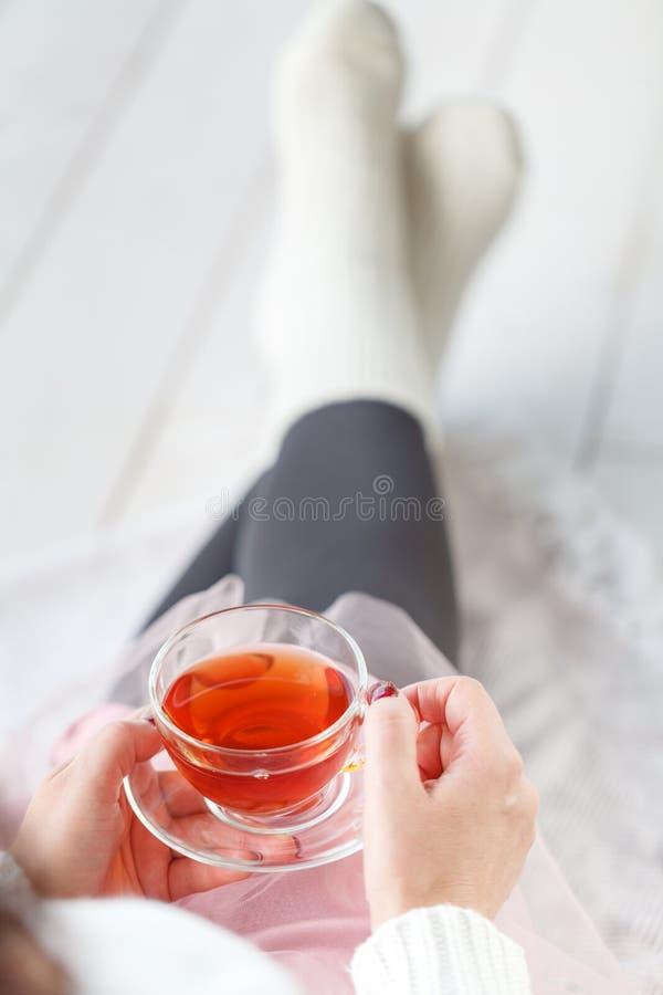 Donna con il plaid di resto del tè della tazza, piede con i calzini bianchi fotografie stock