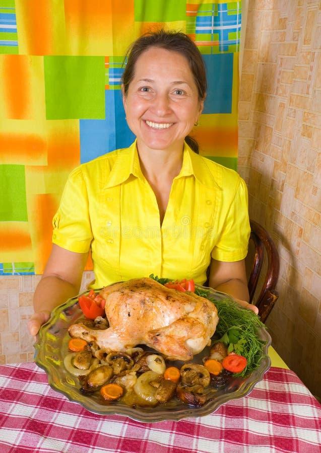 Donna con il pollo cucinato fotografia stock libera da diritti