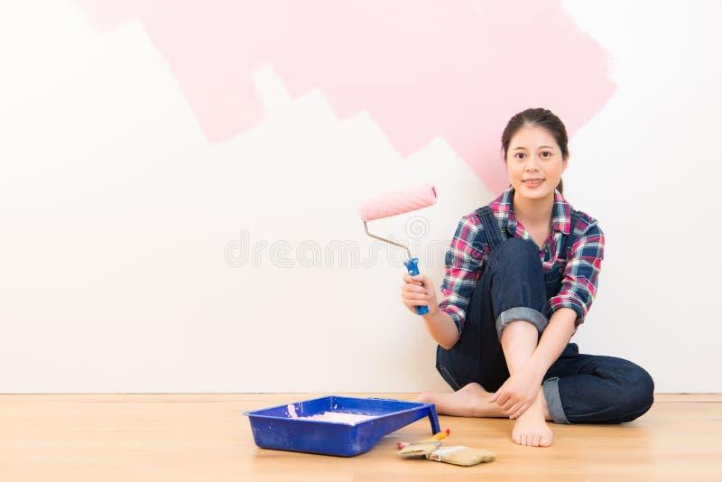 Donna con il rullo che applica pittura rosa immagine stock