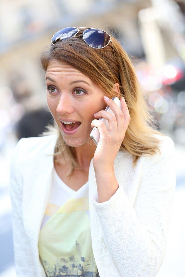 Donna con il sembrare sorpreso che parla sul telefono immagini stock libere da diritti