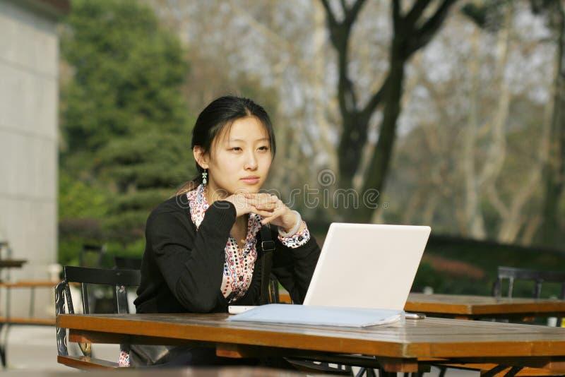 Donna con il suo computer portatile immagine stock