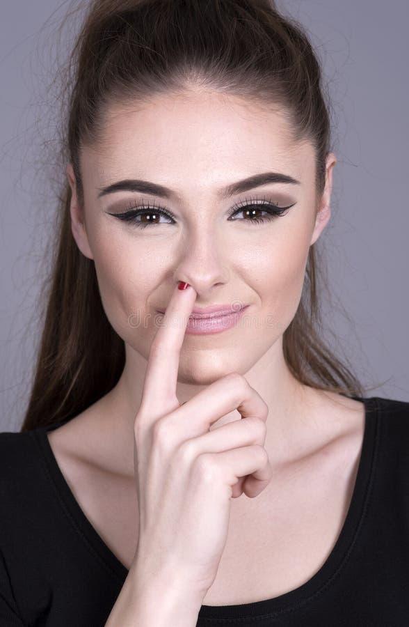Donna con il suo dito sul suo naso fotografia stock libera da diritti