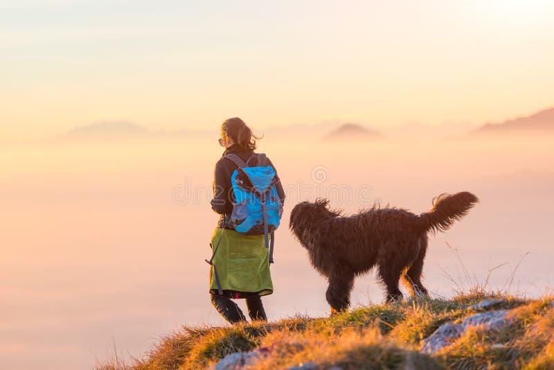 Donna con il suo pastore nero che cammina nelle montagne immagine stock