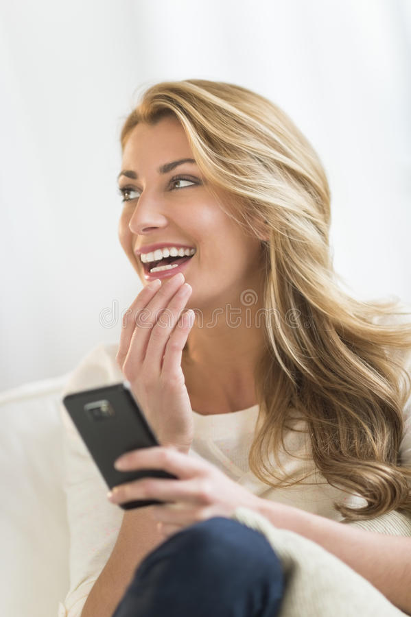 Donna con il telefono cellulare che distoglie lo sguardo a casa fotografia stock libera da diritti