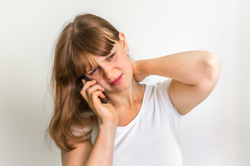 Donna con il telefono cellulare che ha dolore nel suo collo fotografia stock