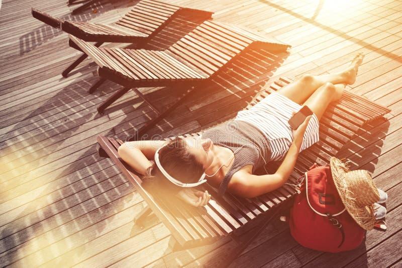 Donna con il telefono cellulare che riposa sullo sdraio e sulla musica d'ascolto immagine stock