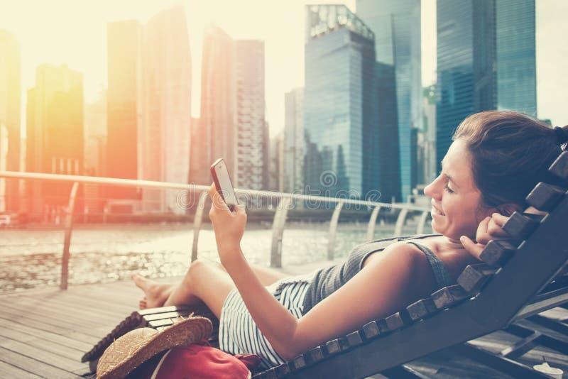 Donna con il telefono cellulare che riposa sullo sdraio nel centro urbano immagini stock