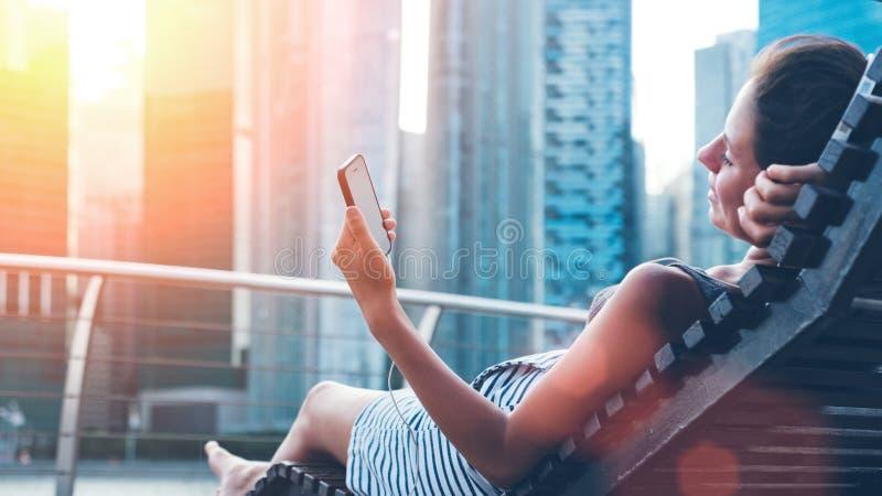 Donna con il telefono cellulare che riposa sullo sdraio vicino in città immagini stock libere da diritti