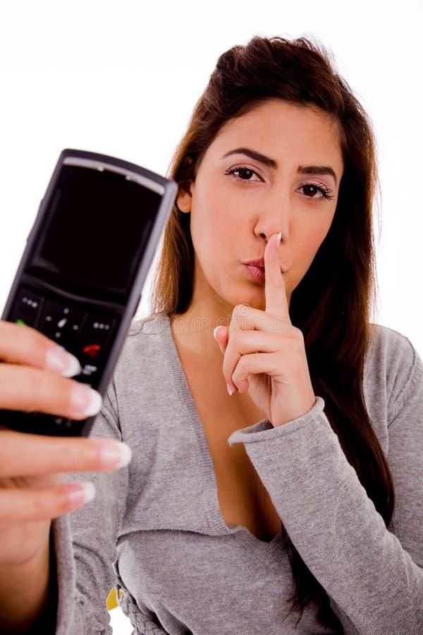 Donna con il telefono delle cellule che insegna per essere silenzioso immagine stock libera da diritti