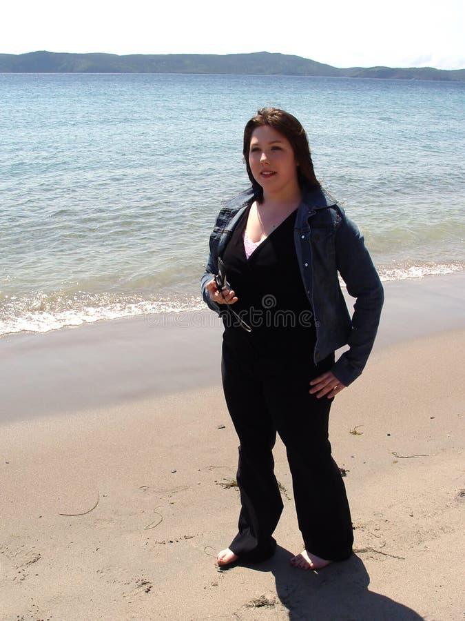 Donna con il telefono delle cellule sulla spiaggia fotografia stock